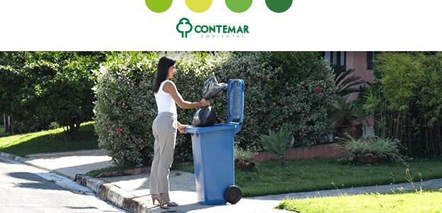 Mulher colocando resíduos em um contentor em frente a sua casa para ilustrar como reduzir o lixo